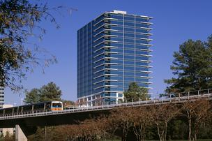 A MARTA train takes commuters by a Perimeter office building.