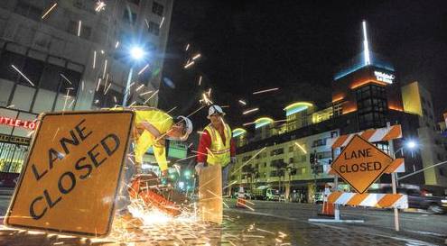 Workers cut loose metal plates in a project to relocate DWP lines for the Metro's expansion. Mayor Eric Garcetti said the Metro extension along Wilshire Boulevard is the nation's largest public works program and his top priority. (Ricardo DeAratanha / Los Angeles Times)