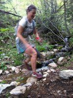 picture of missy berkel crossing a stream keeping her feet dry