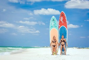 2 girls holding paddle boards