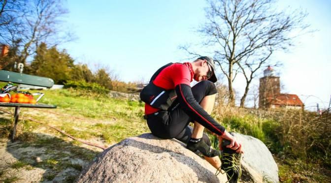 Lars Michael Sørensen fra Trailcast sidder på en sten og tømmer sine løbesko for sand.