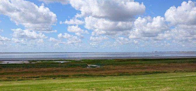 Udsigt til Fanø fra det sydlige Jylland. flotte skyer og grønt græs.