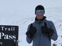 Moses Løvstad med to tommelfingre i vejret. Han står ved siden af et skilt, som fortæller at han er på toppen af Rainy Pass, Alaska