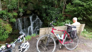 Man sitting on a bench near a waterfall with bicycles behind the bench