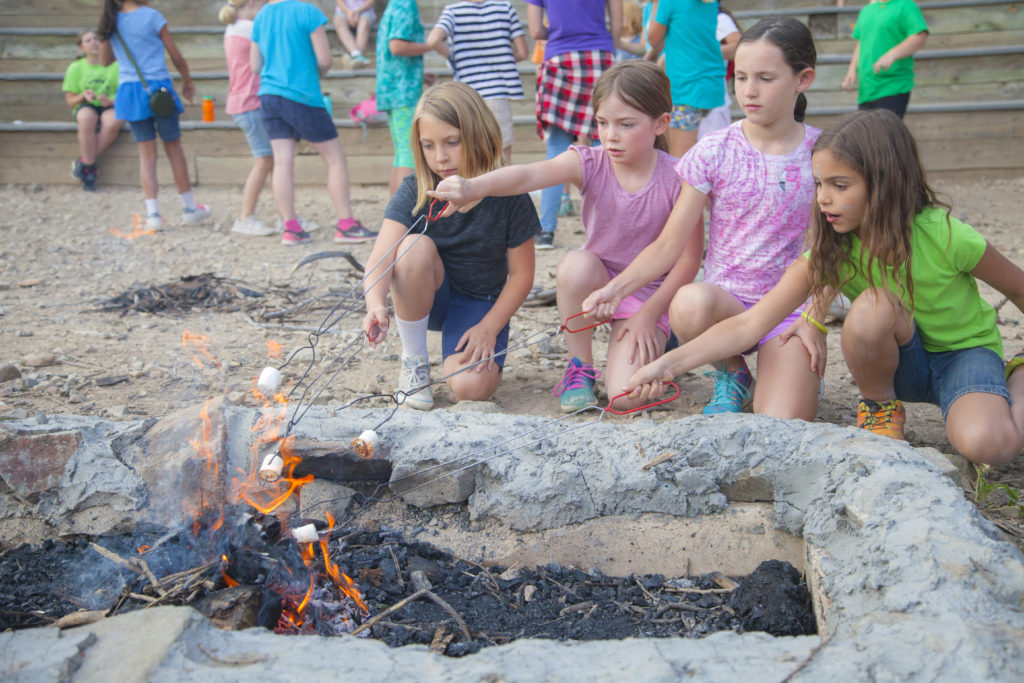 Girls roasting s'mores at camp