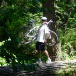 mountain biker carrying bike across log