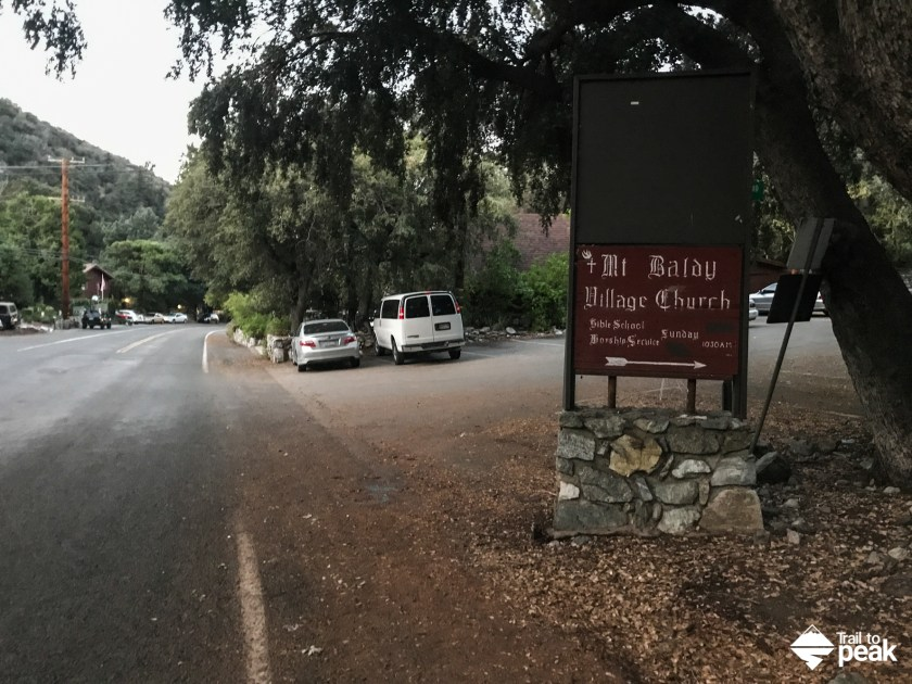 To hike Mt. Baldy via Bear Canyon, drive to 6777 Mt Baldy Rd, Mt Baldy, CA 91759. You'll park on the west side Mt. Baldy Rd, right outside of the US Forestry Department and Mt. Baldy Visitor Center. Once you've parked, walk south towards the Mt. Baldy Lodge Restaurant and go right (west) onto Bear Canyon Dr. You'll walk on Bear Canyon Dr for .4 miles before reaching the sign for Mt. Baldy Trail.