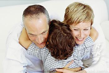 Boy hugging grandparents