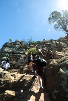Group of people climbing lions head on a beautiful day in cape town, south africa