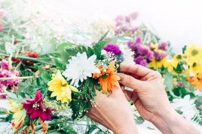 Flower arranging workshop, a woman making a fresh floral crown arrangement.