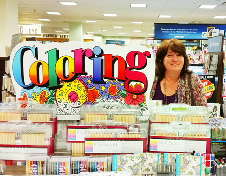 Robin at a table filled with coloring books