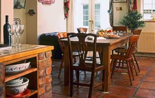 Solid wooden dining table and chair in rustic kitchen interior with wood-beamed ceiling and curtain swags