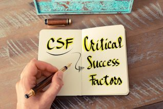 Retro effect and toned image of a woman hand writing a note with a fountain pen on a notebook. Business Acronym CSF as Critical Success Factors as business concept image