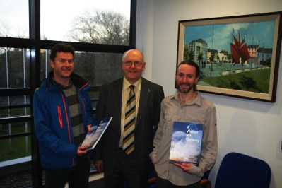 Galway City Council Chief Executive (City Manager) Brendan McGrath accepting a copy of 'A Vision for Galway 2030' from Kieran Cunnane and Bernard McGlinchey of Transition Galway