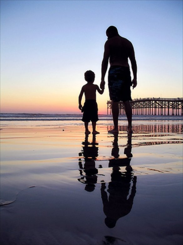 The father and son duo walked hand in hand on the beach..