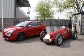 60 years on - Iconic Alfa 158 with Alfa MiTo Cloverleaf outside the British Racing Drivers Club, Silverstone Motor Racing Circuit.