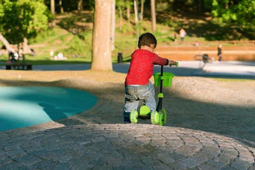 Young Child riding 3 wheel kick scooter at park