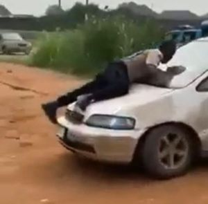 An FRSC Official clinging to the bonnet of a moving Honda car.