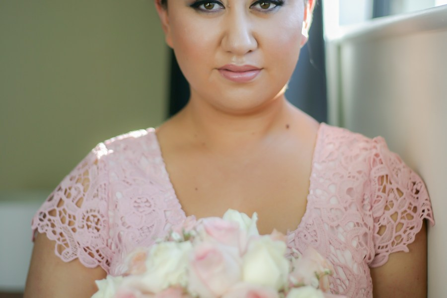 Sydney wedding bride looks at camera with bouquet
