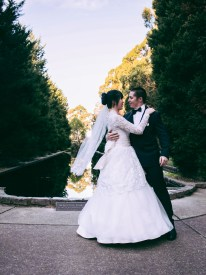 Australian and asian wedding couple look at each other as groom holds her