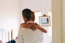groom's mum hugs her son during wedding day
