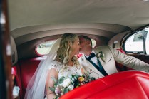 bride and groom in vintage wedding car kissing