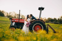 bride and groom kiss on a tractor in countryside new south wales
