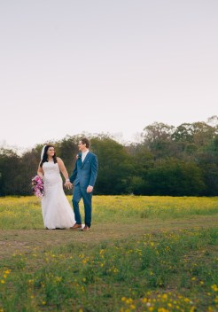 bride and groom walk in countryside on dirt track