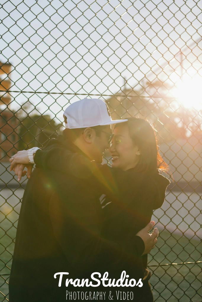 Beautiful engaged couple hugging in the sunset