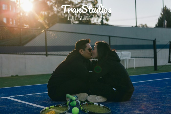 beautiful engaged couple sitting under the sunset at tennis court