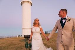 Beautiful wedding couple at wollongong lighthouse at sunset walking
