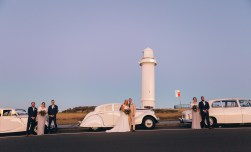 beautiful bridal party and wedding couple standing next to wedding cars at wollongong lighthouse sunset
