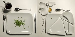 Two plates are side by side, one with a couple of peas, the other broken into pieces.