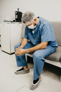 A male doctor wearing scrubs, hairnet and mask sits with folded hands and looks down.