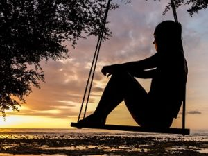 A silhouette of a woman sitting in a rope swing