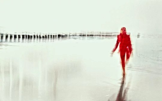 artistic photography showing a blured shiloutte of a girl in red costume