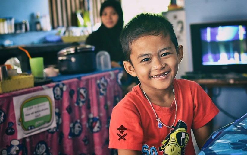 young thai boy without teeth smiling in restaurant in phuket