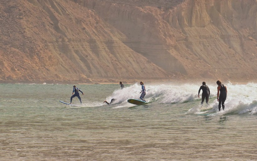 dew surfers in kind of zombie poses rides slow wave with the mountain in the background in morocco imsouane the bay