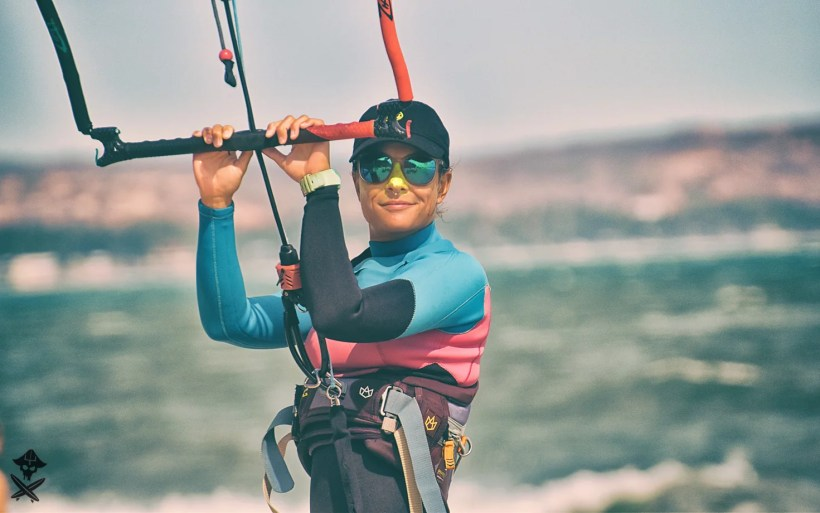 Ola kite girl instructor in sunglasses is standing with the bar in her hands and smiling
