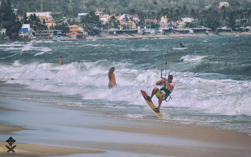 vincent loof doing a transition on the mui ne beach with lieuwe shot gun kite board and mui ne village in background