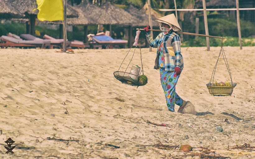 woman in vietnamese hat walks the beach with bucket of fruits and cocos in mui ne vietnam 2018