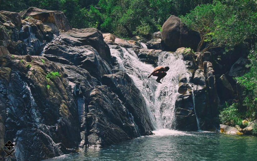 guy is jumping from the rock in the waterfall hidden in the jungle of vietnam