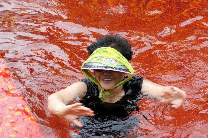 ajumma in visor swimming in red pool