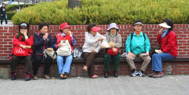 A group of Korean ajummas sitting together on a bench sharing a snack