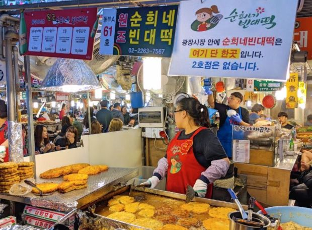 a vendor selling food at Gwangjang Market - unique things to do in Seoul at night