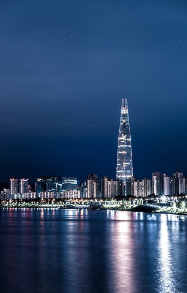 lotte world tower next to the Han River and apartment buildings lit up in seoul at night