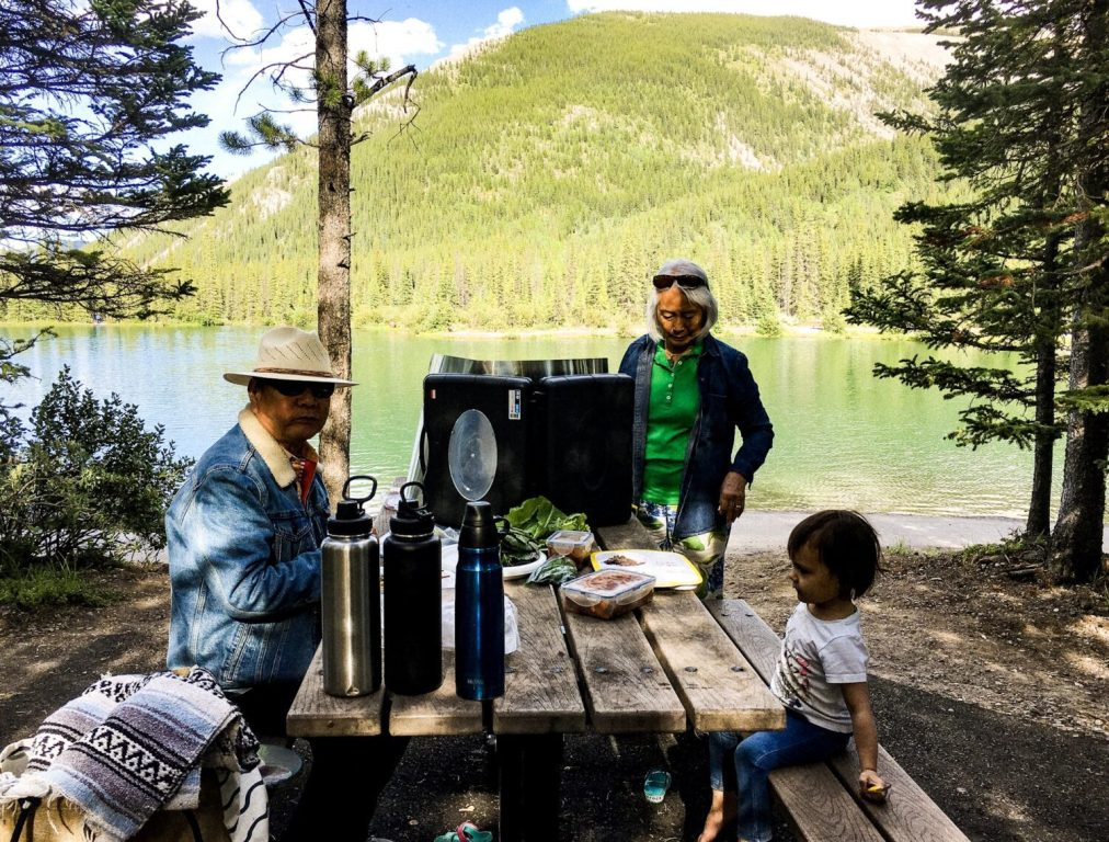 family having a bbq and picnic at forget me not pond in kananaskis
