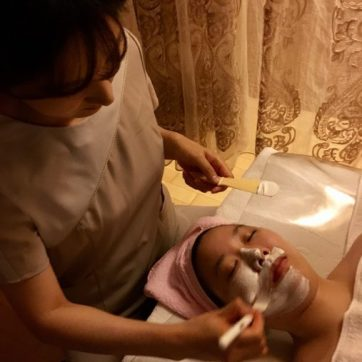 A mask is painted on the face during a Korean facial.