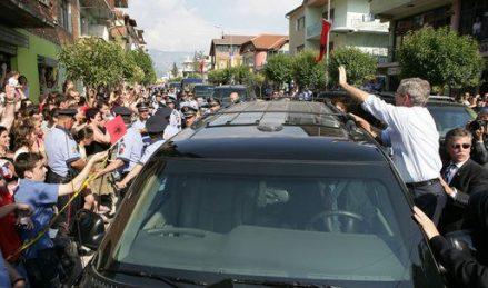 George W. Bush waving at crowds from a car in Fushe Kruje Albania