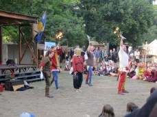 these jugglers have enlisted a hapless volunteer, who doesn't know about the expression on her mask, nor about the swords and flaming torches that are about to be tossed across the circle right next to her head